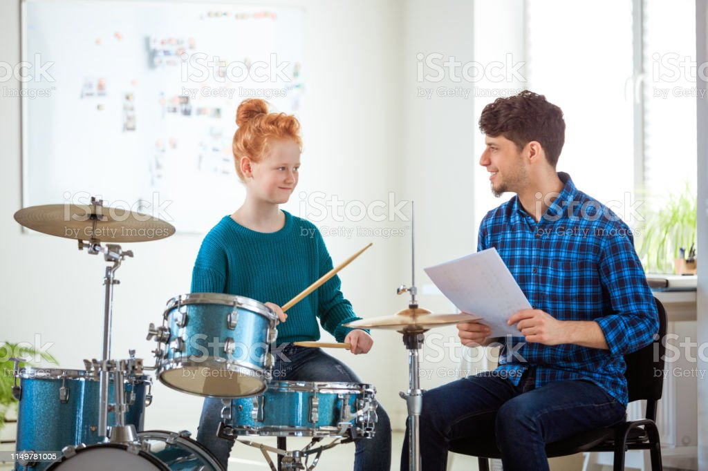 Female drummer looking while practicing by teacher Smiling music teacher holding sheet looking at female student. Pre-adolescent drummer is practicing by instructor. They are in conservatory. 12-13 Years Stock Photo