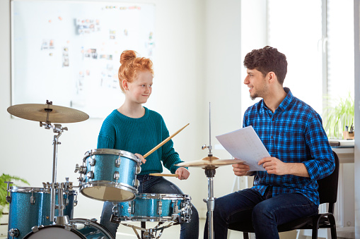 Female Drummer Looking While Practicing By Teacher Stock Photo - Download Image Now