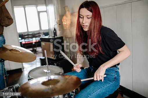 Generation Z Music Band On Rehearsal. Selective focus on female drummer.