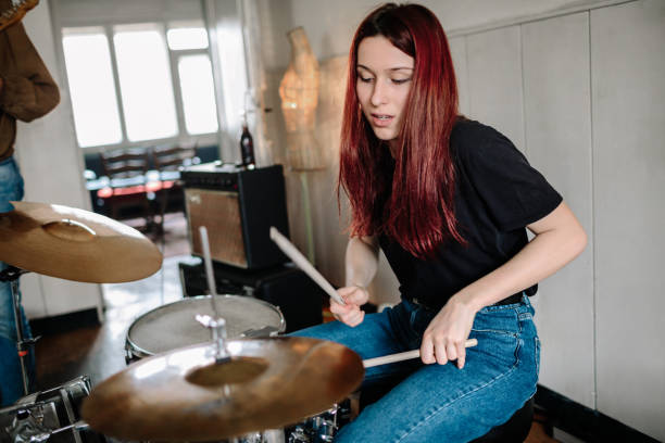 Female Drummer On Rehearsal Generation Z Music Band On Rehearsal. Selective focus on female drummer. drummer stock pictures, royalty-free photos & images