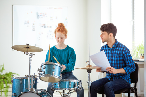 Female Drummer Practicing By Male Music Teacher Stock Photo - Download Image Now