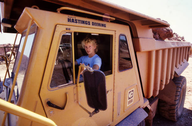 Female dump truck driver sitting in the cab of her huge ore carrying truck stock photo