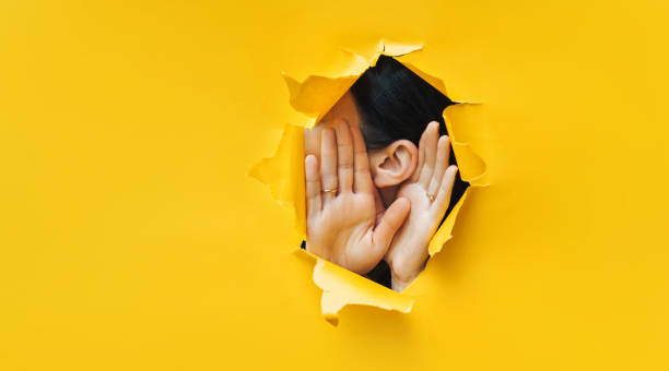 Female ear and hands close-up. Copy space. Torn paper, yellow background. The concept of eavesdropping, espionage, gossip and the yellow press. Female ear and hands close-up. Copy space. Torn paper, yellow background. The concept of eavesdropping, espionage, gossip and the yellow press. confidential stock pictures, royalty-free photos & images