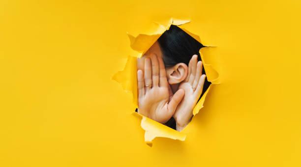 oreja y cierre de las manos femeninas. copiar espacio. papel desgarrado, fondo amarillo. el concepto de espionaje, espionaje, chismes y la prensa amarilla. - cotilleo fotografías e imágenes de stock