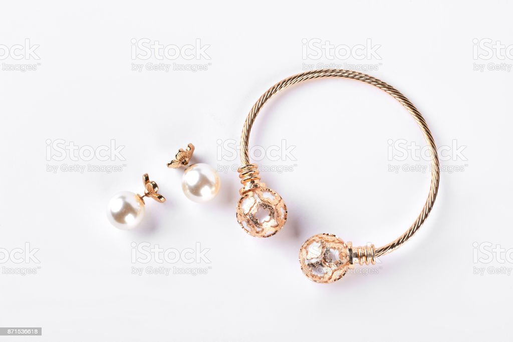 Female earings and bracelet on white background. stock photo