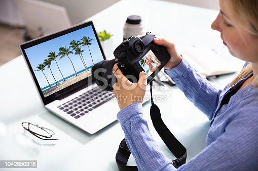 Female Editor Looking At Couple Photograph In DSLR Camera With Laptop On Desk