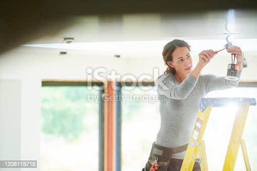 female electrician installing downlights