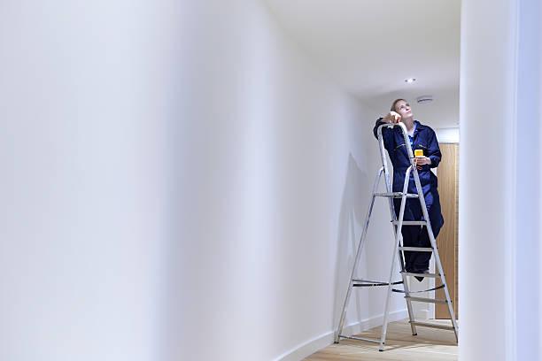 weibliche elektriker installieren lichter in der decke - einbauspots stock-fotos und bilder