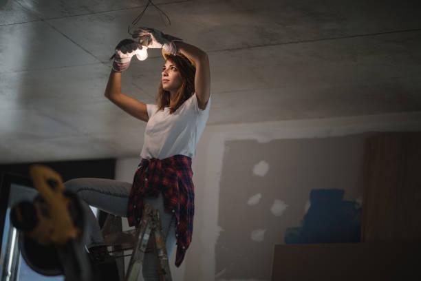 weibliche elektriker glühbirne bei renovierungs anziehen. - glühbirne auswechseln stock-fotos und bilder