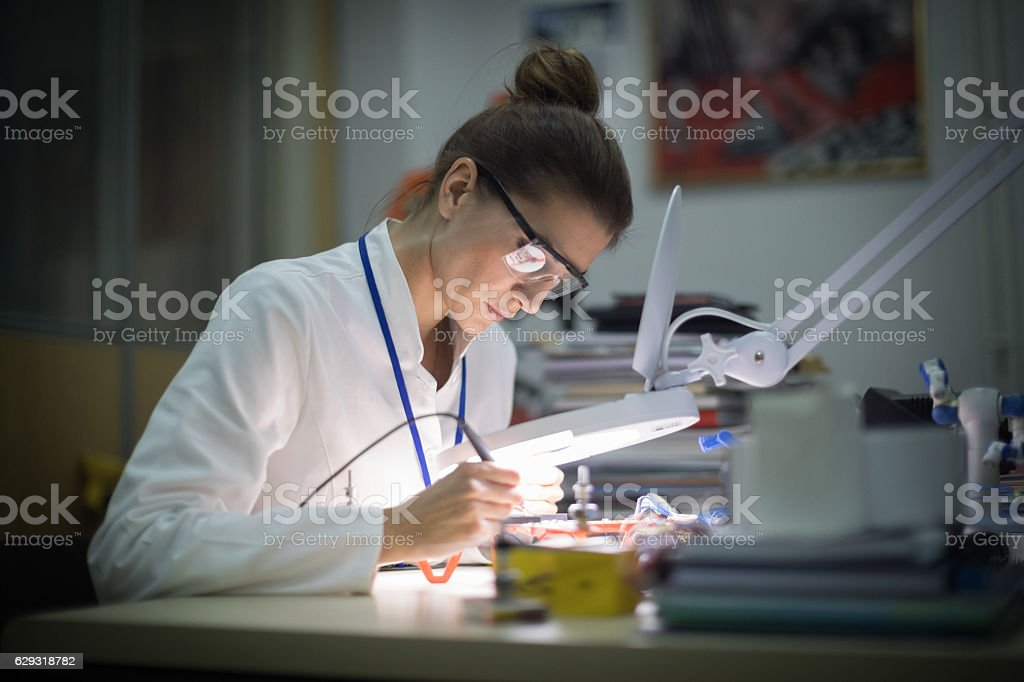 Female electrician using magnifying glass stock photo