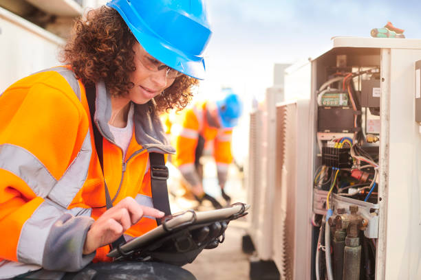 female electrician with aircon unit stock photo