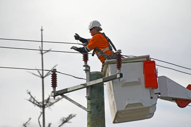 Female electricity worker fixing power line stock photo