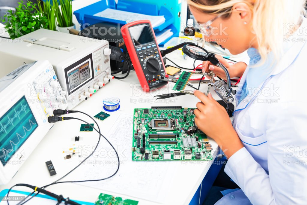 Female electronic engineer checking circuit board in laboratory stock photo