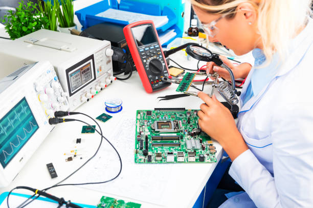 weibliche elektroniker prüfung platine im labor - freizeitelektronik stock-fotos und bilder