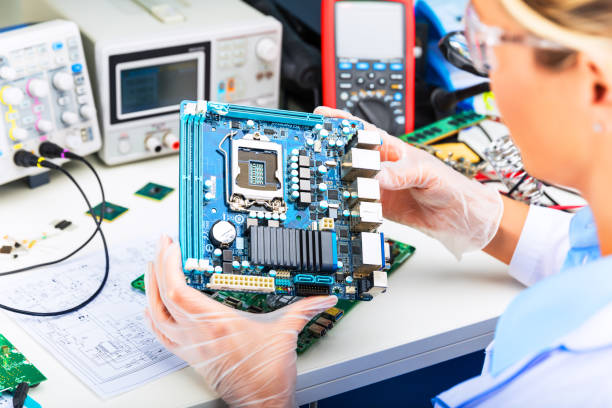 female electronic engineer examining computer motherboard in laboratory - przemysł elektroniczny zdjęcia i obrazy z banku zdjęć