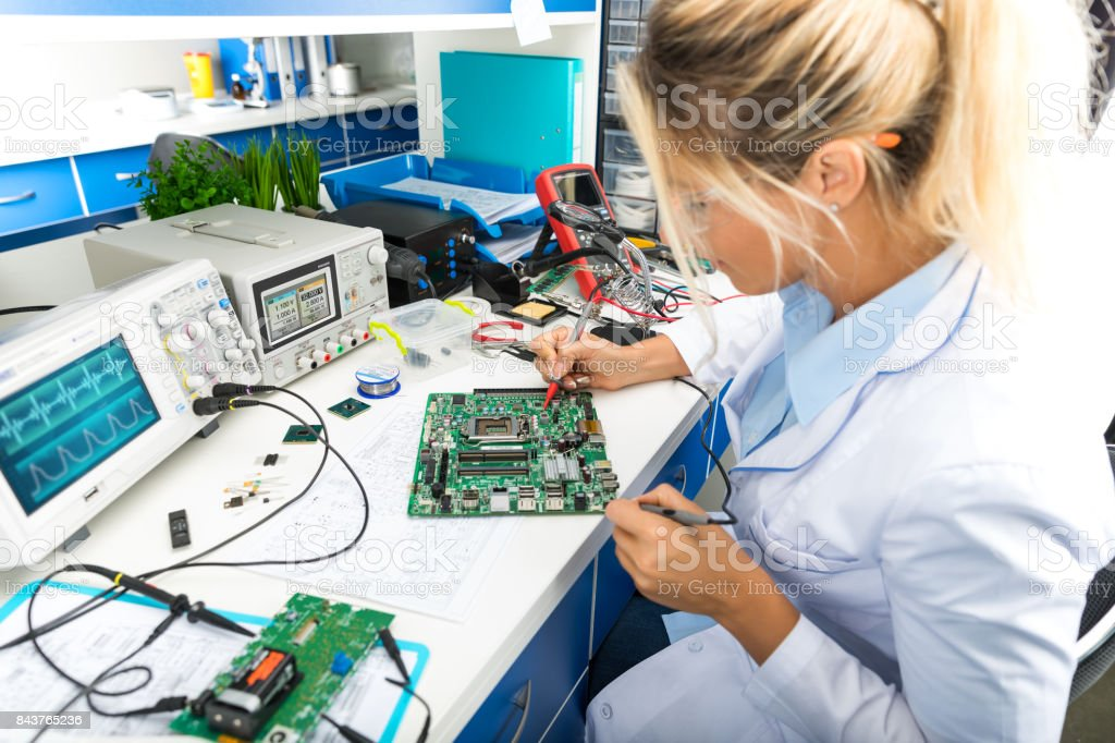 Female electronic engineer testing computer motherboard in laboratory royalty-free stock photo