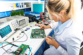 Young female digital electronic engineer testing computer PC motherboard in laboratory