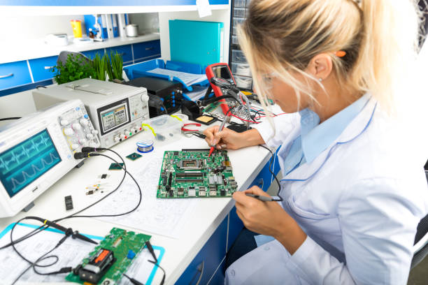 Female electronic engineer testing computer motherboard in laboratory stock photo
