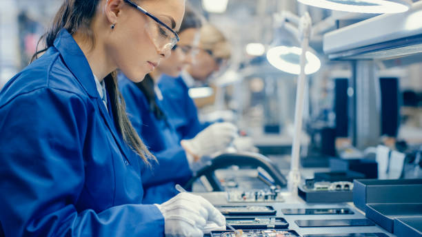 female electronics factory workers in blue work coat and protective glasses assembling printed circuit boards for smartphones with tweezers. high tech factory with more employees in the background. - electronics industry stock pictures, royalty-free photos & images