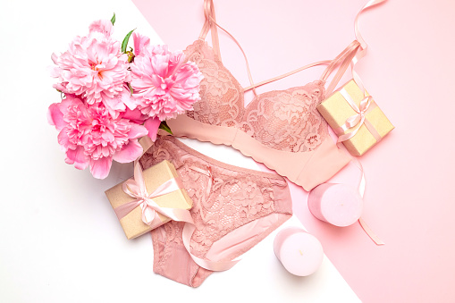 Female elegant pink lace bra and panties, flowers pink candles, a bouquet of beautiful peonies top view