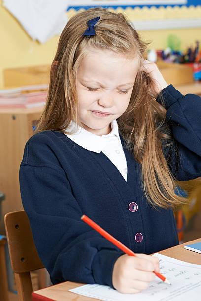 female elementary pupil suffering from head lice in classroom - kopfläuse was tun stock-fotos und bilder