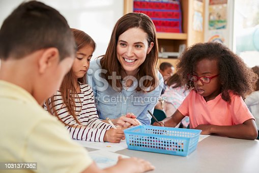 Female elementary school teacher and kids in class, close up