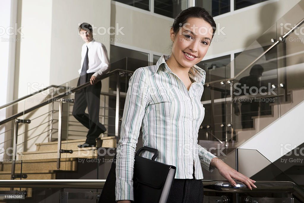 Female employee carrying briefcase posing on stairwell stock photo