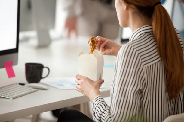女性従業員のオフィス作業休憩中にアジアの麺を食べる - 昼食 ストックフォトと画像