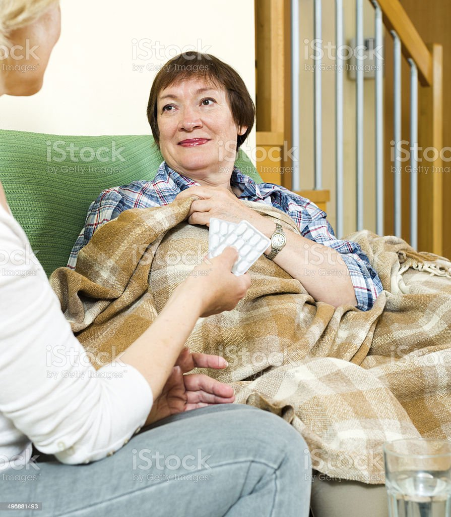 female employee gives a sleeping pill to woman stock photo