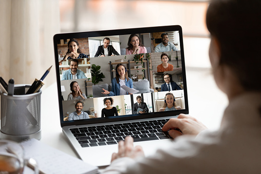 Rear close up view of female employee brainstorm talk on video call with diverse colleague on laptop. Woman speak engaged in team group discussion, have webcam company online meeting or briefing.