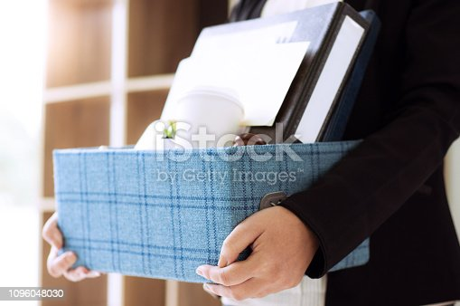istock female employee packing box for quit a job 1096048030