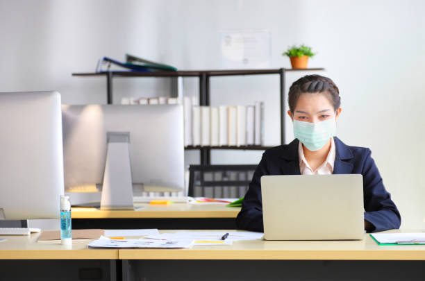 Female employee wearing medical face mask while working in the business office during covid-19 pandemic Female employee wearing medical face mask while working alone because of social distancing policy in the business office during coronavirus or covid-19 outbreak pandemic situation pandemic illness stock pictures, royalty-free photos & images