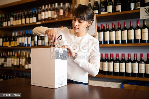 Young woman at wine store opening a cardboard box. Female employee working at wine shop.
