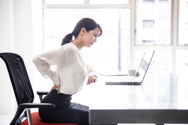 Female employees are suffering from low back pain stock photo