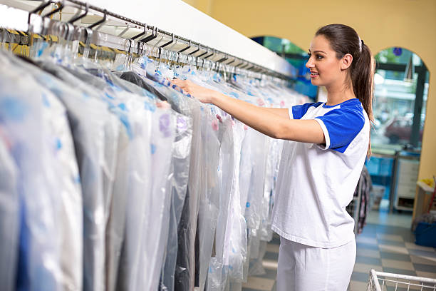 Female employees checks clothes - foto de acervo
