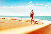 Sporty female runs on a road near the sea in a tropical climate while the sun shines. Her exercising is pushing her endurance for marathon running or a triathlon. She looks calm, as she runs in the heat.