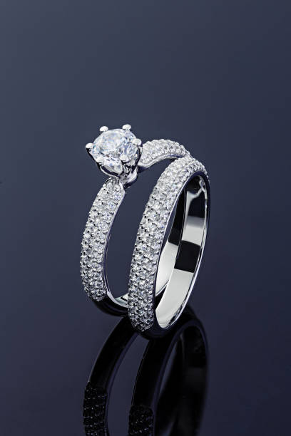 Female engagement and wedding rings with diamonds on black background