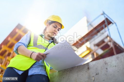 Female, Latin descent engineer, foreperson, or inspector checks blueprints inside a construction job site. She is wearing  with safety vests and hard hat/helmet