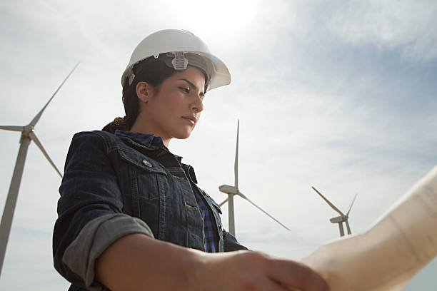 Female engineer at wind farm with plans  wind power stock pictures, royalty-free photos & images