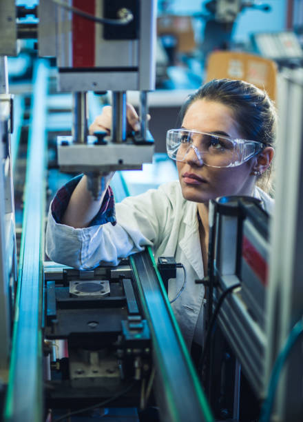 Female engineer examining machine part on a production line. Quality control worker analyzing machine part on a manufacturing machine. stem topic stock pictures, royalty-free photos & images