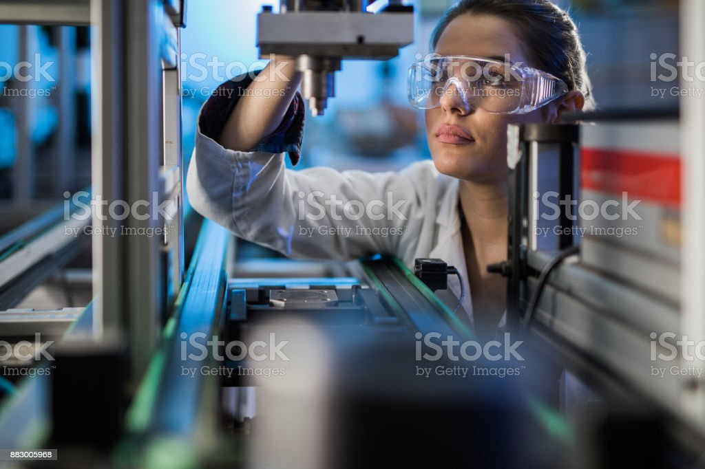 Female engineer examining machine part on a production line. stock photo