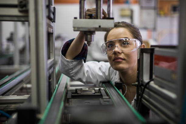 female engineer examining machine part on a production line. - electronics industry stock pictures, royalty-free photos & images