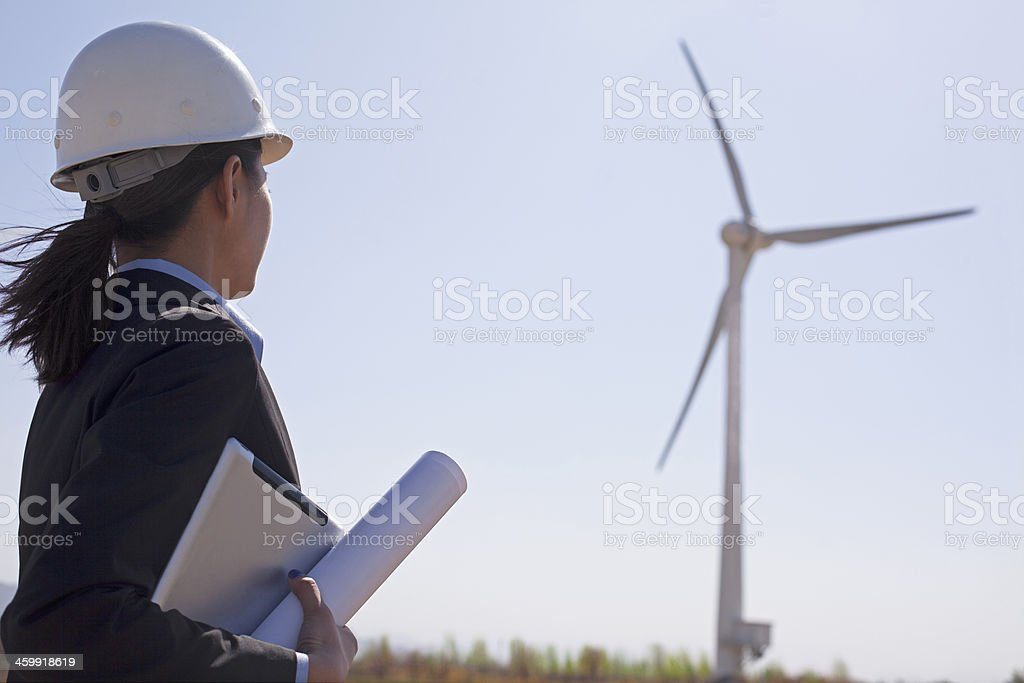 Female engineer holding blueprints and checking wind turbines on site, stock photo