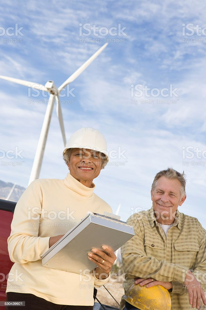 Female Engineer Holding Clipboard Standing With Coworker At Wind royalty-free stock photo