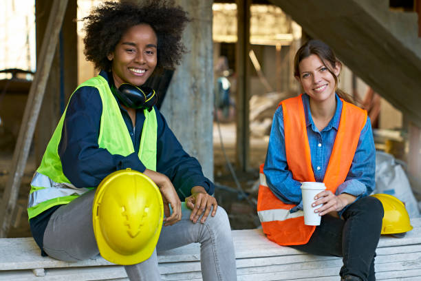 Female engineer holding coffee by coworker stock photo
