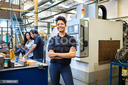 Portrait of smiling female worker standing with her arms crossed at company shop floor with people working in background. Female engineer standing in manufacturing company.