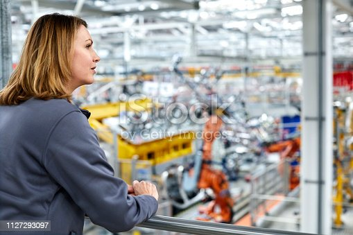 Thoughtful female engineer looking away in car plant. Young worker is standing by railing. She is leaning on railing in factory.