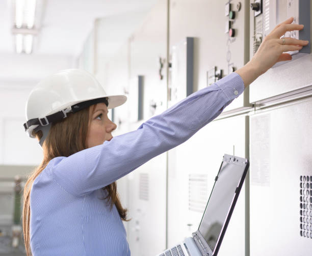 Female engineer operating on equipment in power substation stock photo