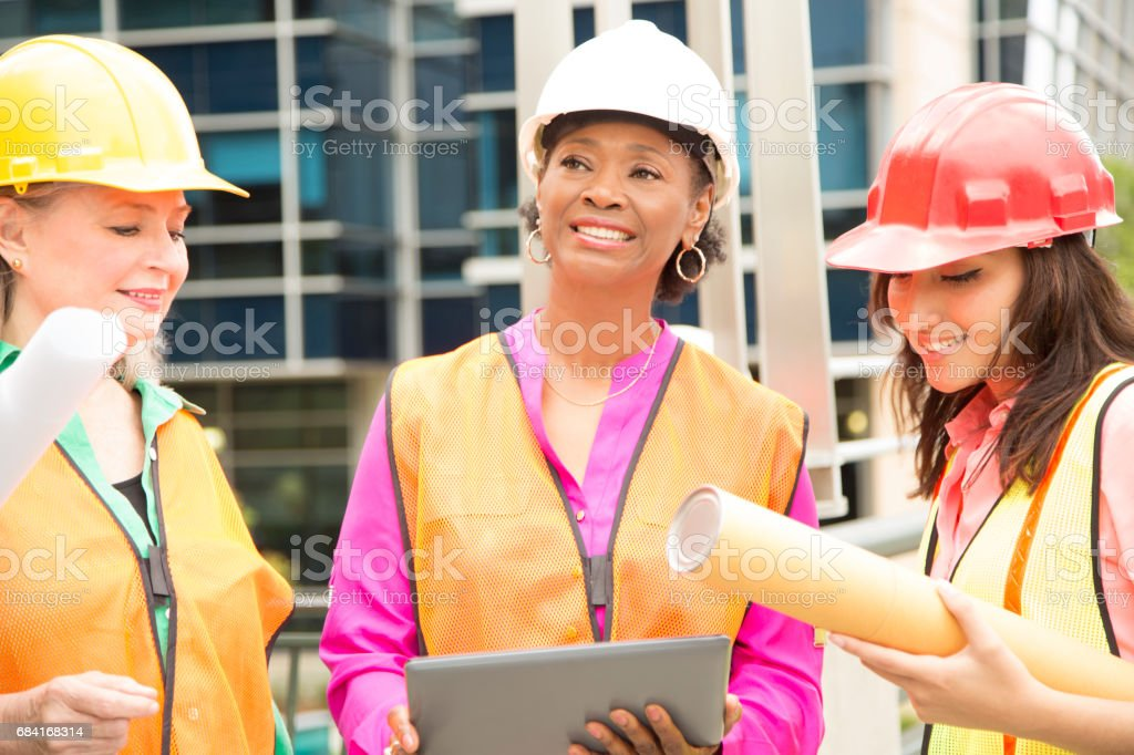 STEM Female engineer or architect team working on a construction project in city. stock photo