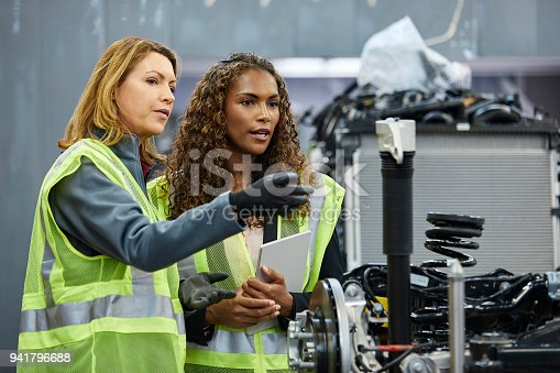 941796726istockphoto Female engineer pointing to colleague at factory 941796688